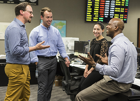Smiling employees engaged in work discussion on Valero trading floor