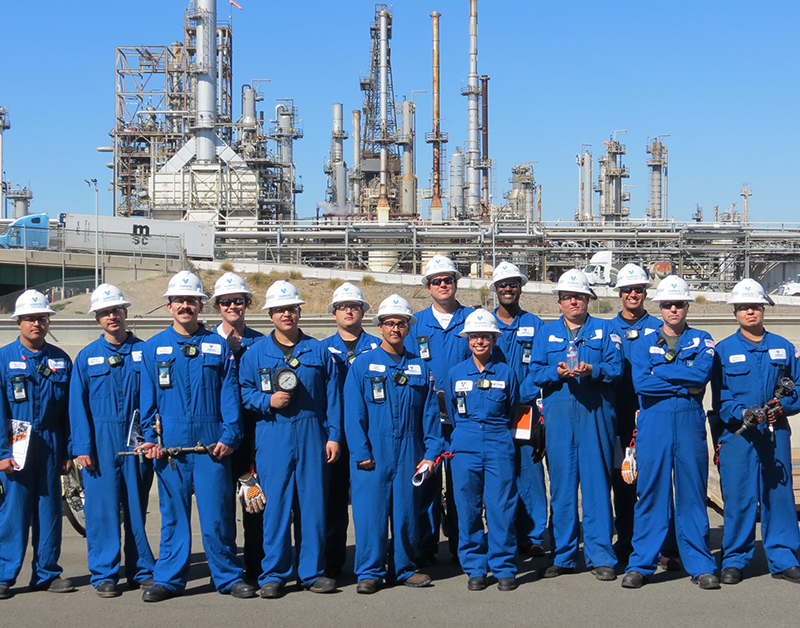 Operators in blue nomex grouped for a photo in front of refinery