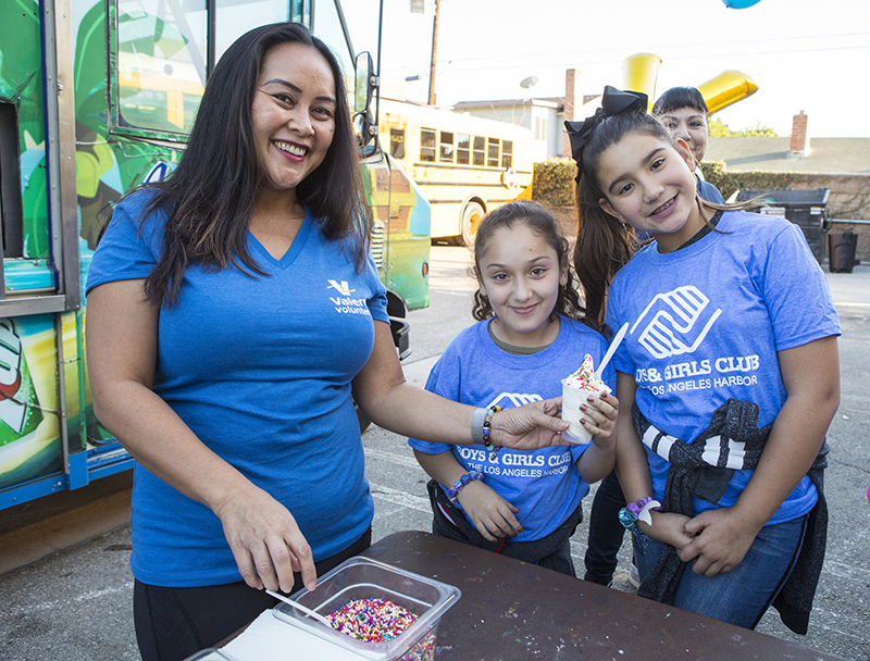 A Valero mentor stands with school children during a volunteer event