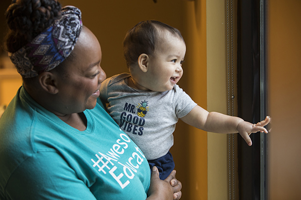 A Valero Family Center caregiver holds an infant to look out of a window