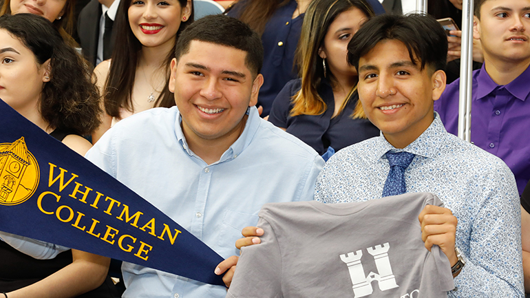 High school students part of the YESS program hold college pennants and celebrate their college goals