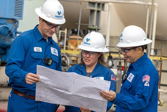 Operators working together, reviewing refinery plans near a refining unit.
