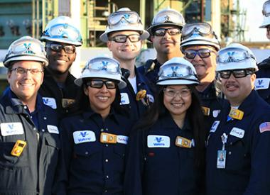 Operations team grouped together smiling in front of refining units